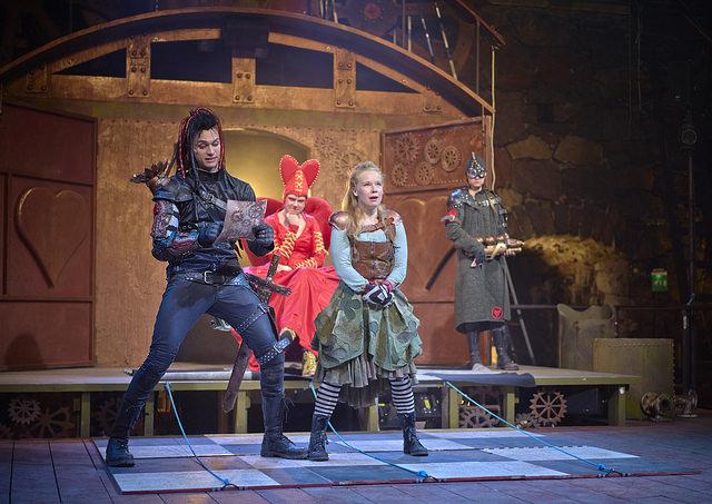 Alice (Anna-Riikka Rajanen) tuomiolla. Etualalla Herttajätkä (Eino-Heiskanen), taustalla Herttakuningatar (Sirja Sauros) ja sotilas (Sonja Salminen). Kuvan oikeudet omistaa Ryhmäteatteri, kuvaaja Johannes Wilenius.