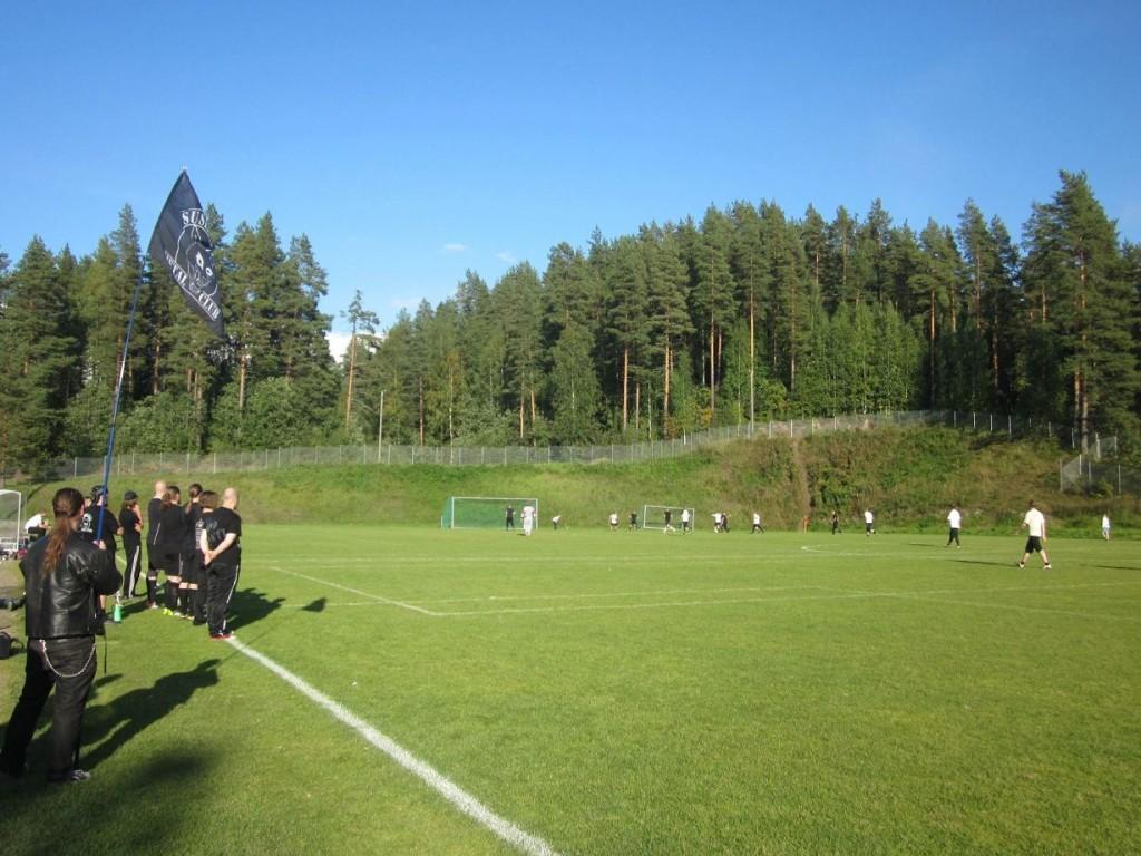 Jalkapallo-ottelu SMC vs. Ravintola La Barre kesällä 2014. SMC pelaa mustissa ja Barre valkoisissa. Etualalla myös SMC:n hallituksen puheenjohtaja SMC:n lipun kanssa.