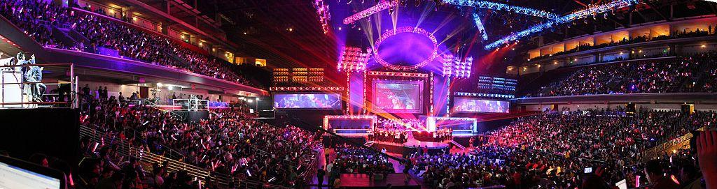 League of Legendsin maailmanmestaruusfinaali. Täyteenpakattu areena, pinkkejä värivaloja, keskellä pelaajat ja suuri valkokangas jolta ottelu näkyy katsojille.