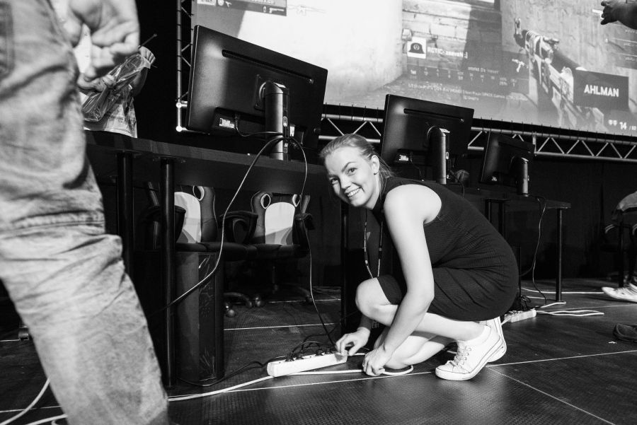 Miisa Nuorgam laittamassa tietokoneiden töpseleitä kiinni jatkojohtoon. Taustalla näkyy rivi pelikoneita ja niiden näyttöjä, sekä valkokangas jolla Counter Strike: Global Offensive -pelin kuvaa.