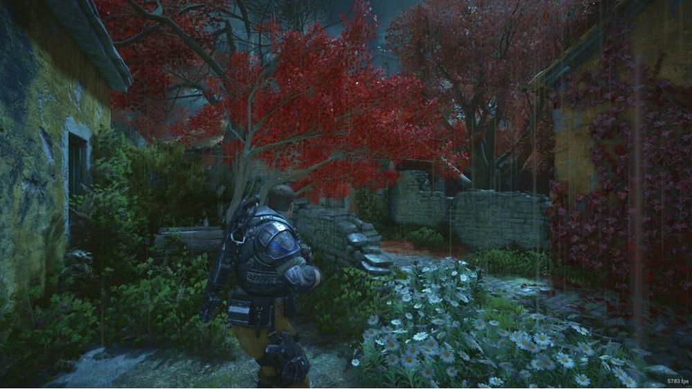 JD seisoo ränsistyneiden, vanhanaikaisten kivirakennusten välissä. Joka puolella on pensaita, puita ja kukkia.