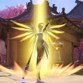 Overwatchin Mercy-hahmo valonsäteen keskellä, siivet levällään kuin enkelillä.