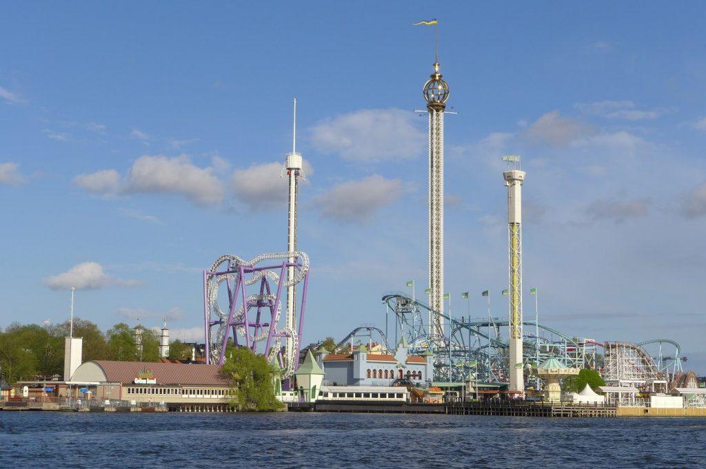 Gröna Lundin huvipuisto sijaitsee Djurgårdenin saarella. Sen laitteet ja tornit kohoavat kuvassa vasten sinistä taivasta.