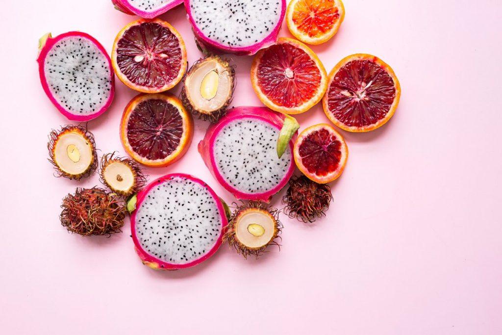 Ylhäältä kuvattuja hedelmiä vaaleanpunaista taustaa vasten. Osa hedelmistä on isoja, osa pieniä.