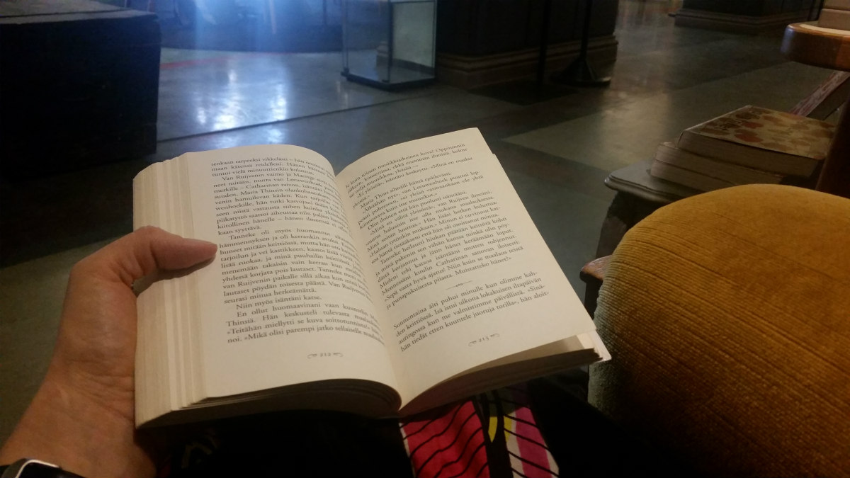 Lukuhetki Rikhardinkadun kirjastossa. Tracy Chevalier: Tyttö ja helmikorvakoru (5/2019). Kuvassa näkyy avointa kirjaa sylissä pitelevä käsi, taustalla hämyinen kirjastosali.