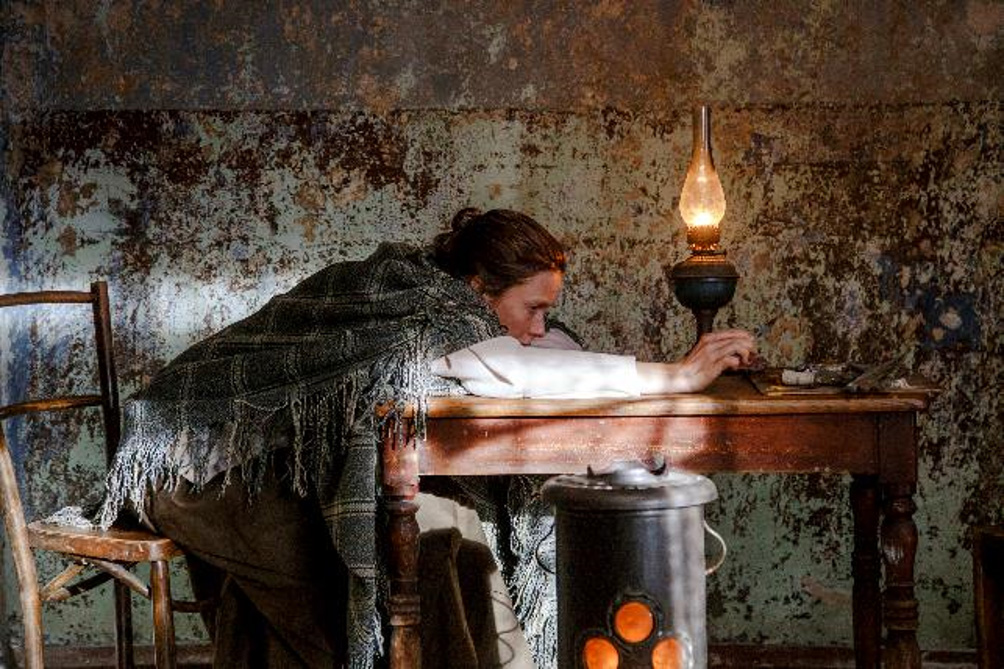 Kuva elokuvasta, Helene istuu vilttiin kääriytyneenä ja nojaa pöytään. Kuva: Andres Teiss.