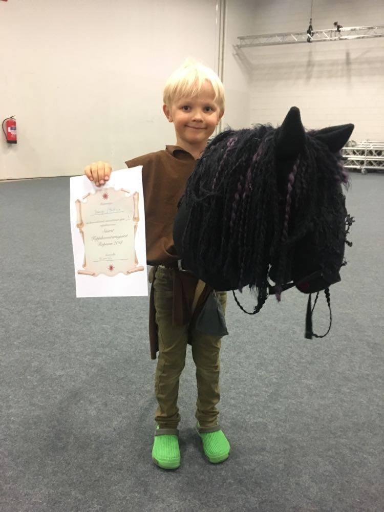 Lapsi poseeraa keppihevosen kanssa.