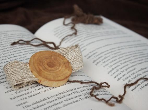 Kuvassa puun poikkileikkauksesta tehty rannekoru Myrskynsilmä-kirjan aukeaman päällä.
