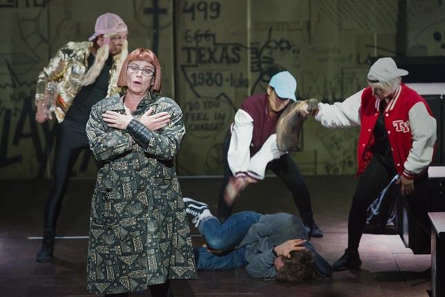 Kuva näytelmän kohtauksesta, jossa opettaja katsoo yleisön suuntaan, ja hänen takanaan kolme lasta hakkaa neljättä, joka makaa maassa.