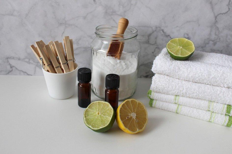 Kuvassa roskattomaan pyykinpesuun liittyviä tavaroita, kuten itse valmistettua pesujauhetta, sitruuna- ja limelohkoja ja puisia pyykkipoikia