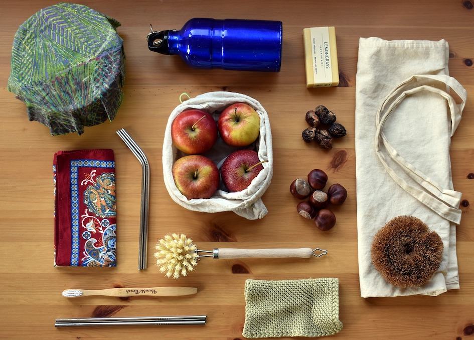 Kuvassa zero wate -tuotteita, kuten kestokasseja, puuvartinen tiskiharja ja hammasharja, metallinen juomapullo ja virkattu tiskirätti