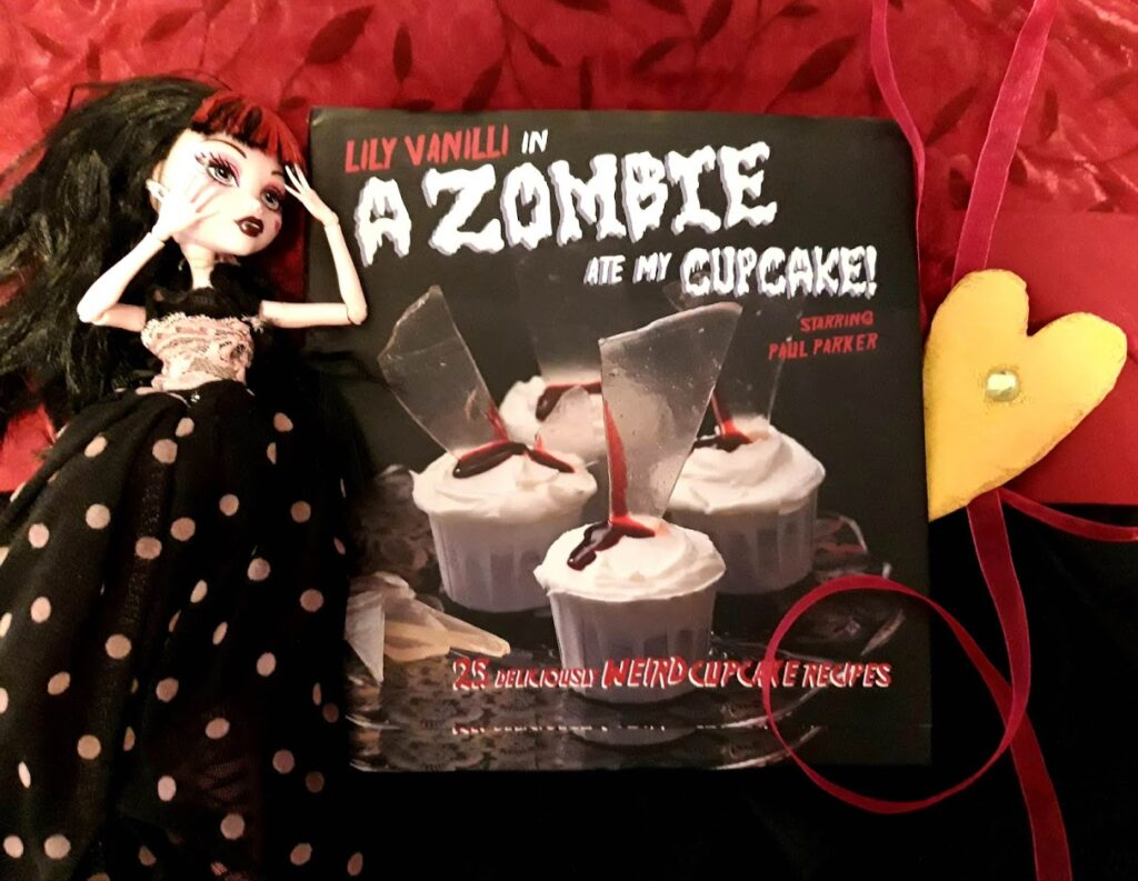 Kuvassa A Zombie ate my cupcake -keittokirja ja kauhuteemäinen nukke.