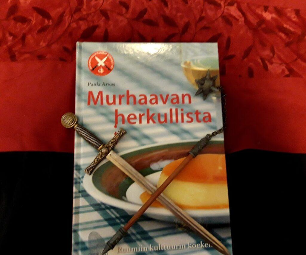 Kuvassa Murhaavan herkullista -keittokirja, miekan muotoinen paperiveitsi ja mini-nuija