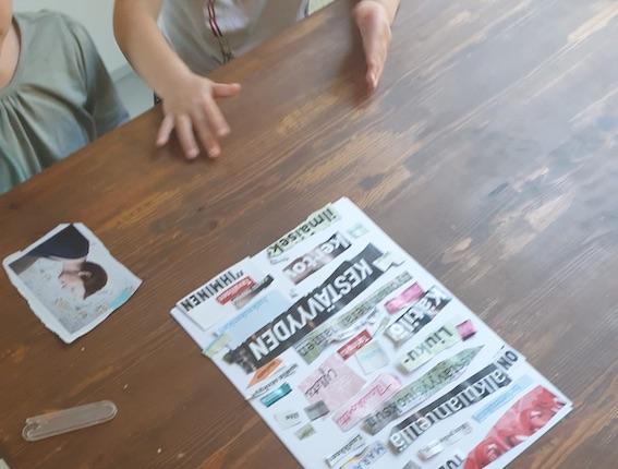 Kuvassa lapset ovat liimanneet lehdistä leikatut sanat paperille