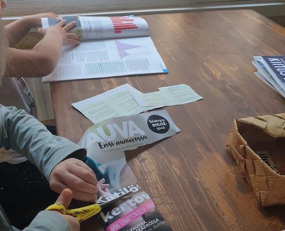 Kuvassa lapset leikkaavat lehdistä sanoja