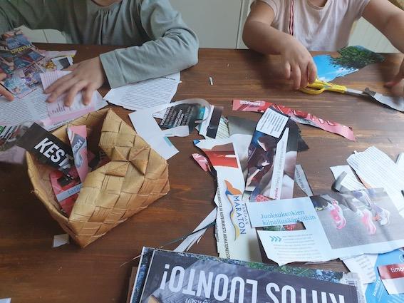 Kuvassa lapsilla on pöydällä edessään iso kasa lehdistä leikattuja sanoja