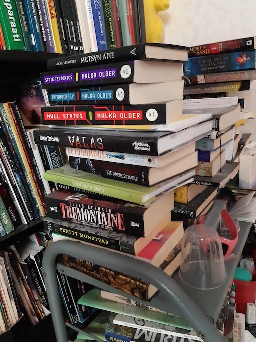 Kuvassa hyllykkö, jolle on pinottu kirjoja