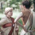 Muinaistyyliseen pukuun pukeutunut nainen katsoo tuimasti vastaavasti pukeutunutta miestä.