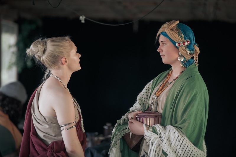 Kaksi naista, joista varsinkin ennustaja pukeutunut runsaisiin koruihin, keskustelee.
