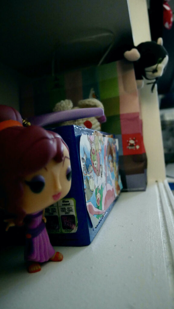 around blue woodenbox there's Megara funko pop figurine and cat doll inside a paper bag