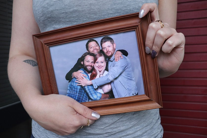 Kuvassa nainen pitelemässä kuvakehyksiä. Kuvakehyksissä valokuva, jossa kolme Supernaturalin päänäyttelijää halaavat kehyksiä pitelevää naista.