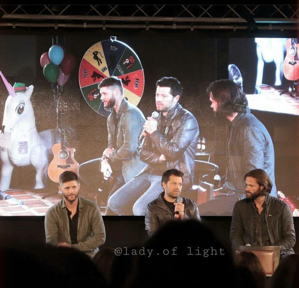 Kuvassa kolme Supernatural-sarjan päänäyttelijää yleisön edessä. Takana videoruutu, jossa heijastettuna sama kuva toisesta kulmasta.