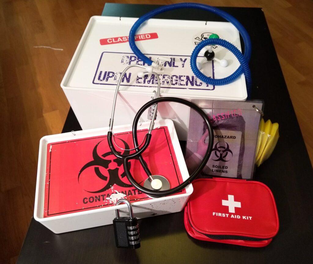 Cryptic Cargo -esineitä, mm. ensiapulaukku, stetoskooppi ja laatikoita.