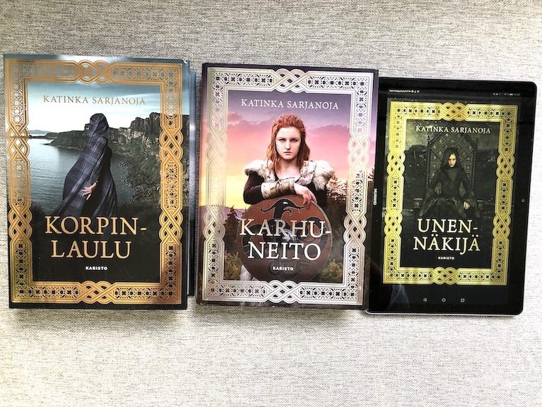 Korpinlaulu- ja Karhuneito-kirjat, sekä Unennäkijä-kirjan kansikuva tabletin näytöllä.