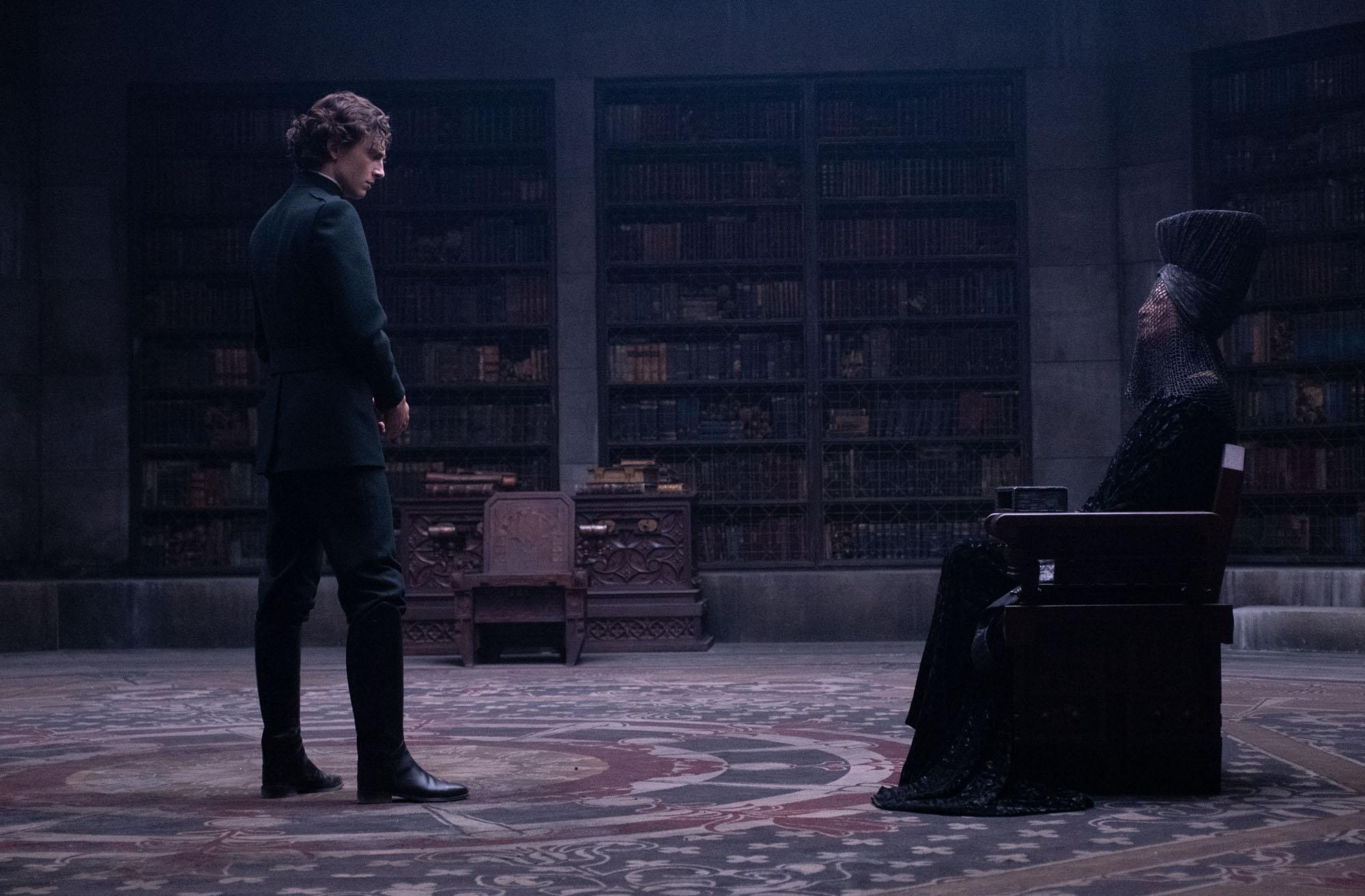 Kirjasto taustana. Paul seisoo tuolissa istuvan isoäitinsä edessä.