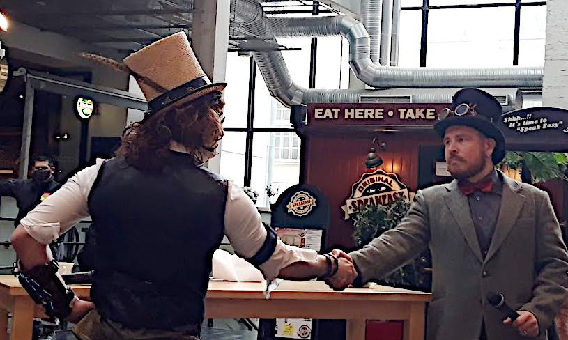 Kuvassa kaksi steampunk-asuista henkilöä kättelee